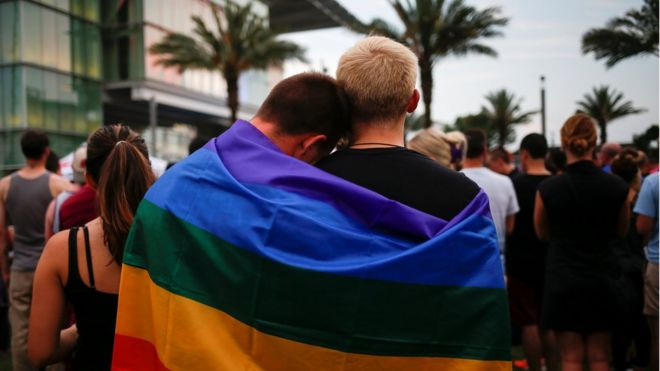 Men, draped in a rainbow flag, embrace ahead of a candle light vigil in memory of victims one day after a mass shooting at the Pulse gay night club in Orlando, Florida