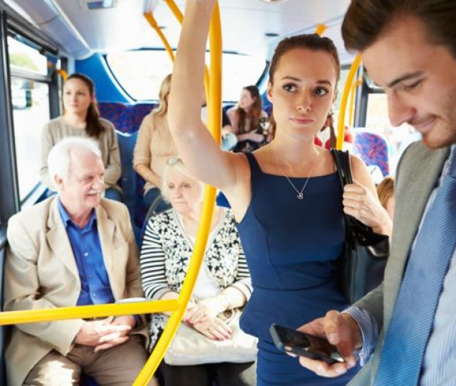 A Man Looks At His Mobile Phone On A Bus A Woman Looks Disapproving