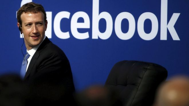 Mark Zuckerberg, wearing a suit and audio earpiece, sits in front of a a Facebook logo