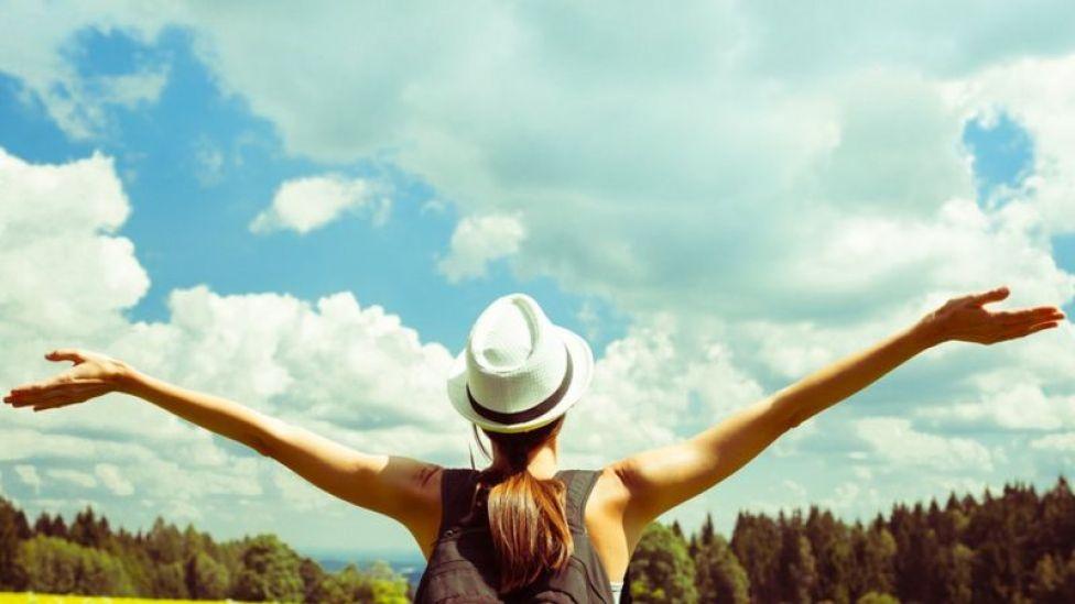 Mujer con brazos estirados hacia el cielo