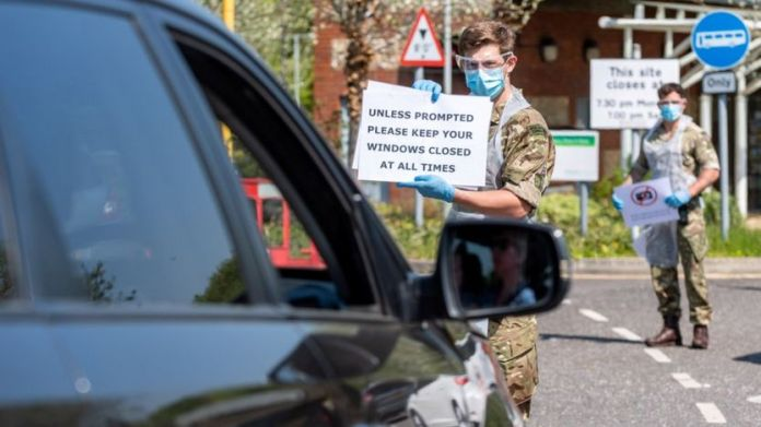 Soldiers give instructions to people in a vehicle at the mobile COVID-19 testing unit, amid the coronavirus disease (COVID-19) outbreak in Salisbury, Britain