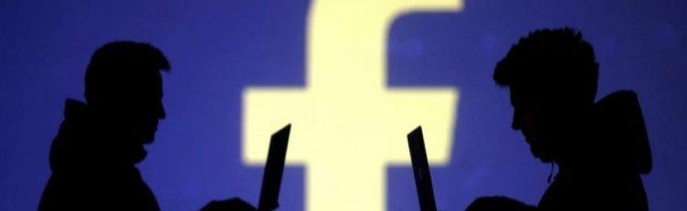 Silhouettes of laptop users are seen next to Facebook logo. File photo
