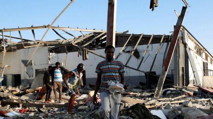 Des migrants ramassent les restes de leurs biens dans les décombres d'un centre de détention pour migrants principalement africains qui a été touché par une frappe aérienne dans la banlieue de Tajoura, dans la capitale libyenne de Tripoli (Libye) le 3 juillet.