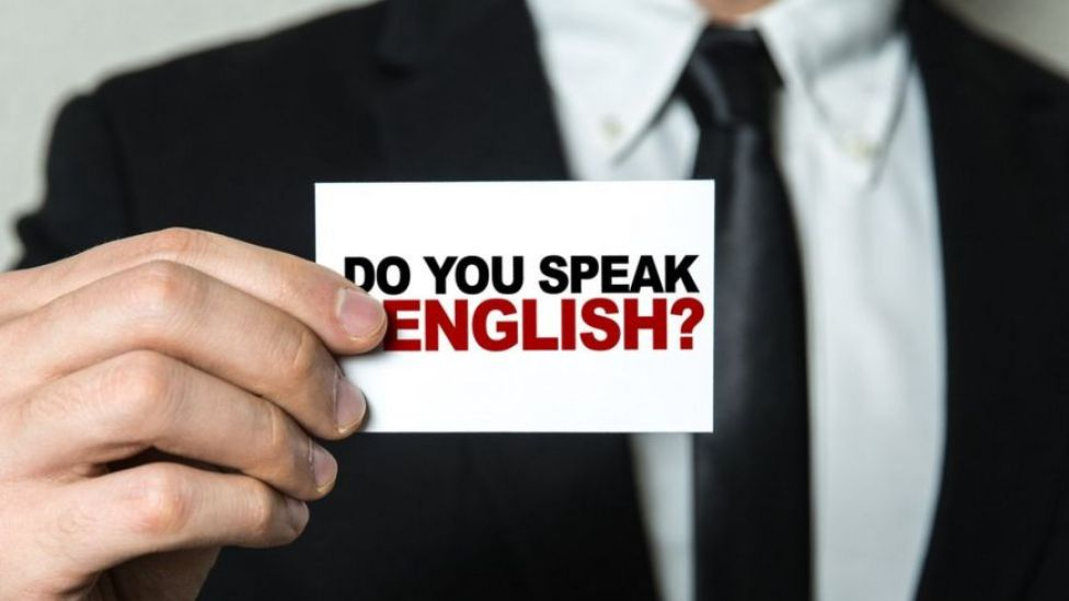 Un hombre sostiene un cartel que dice Do you speak English?