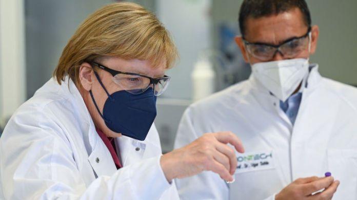 Ugur Sahin, themeluesi dhe drejtori ekzekutiv i kompanisë bioteknologjike BioNTech i tregon kancelares gjermane Angela Merkel ampula marramendëse të vaksinës BioNTech/Pfizer COVID-19 gjatë vizitës së saj në Uzinën e Prodhimit të Vaksinave BioNTech më 19 gusht 2021 në Marburg, Gjermani.