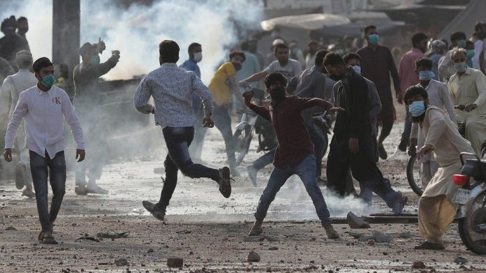 Supporters of Islamic political party Tehreek-e-Labbaik Pakistan (TLP), throw stones at the police during a protest to demand the release of their leader Saad Hussain Rizvi