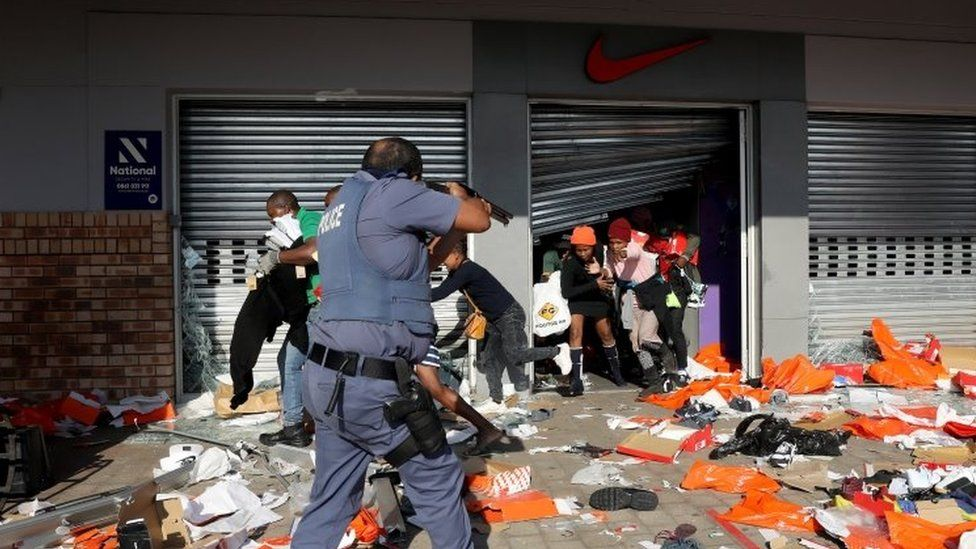 A member of the South African Police Forces tries to control looting during protests in Durban