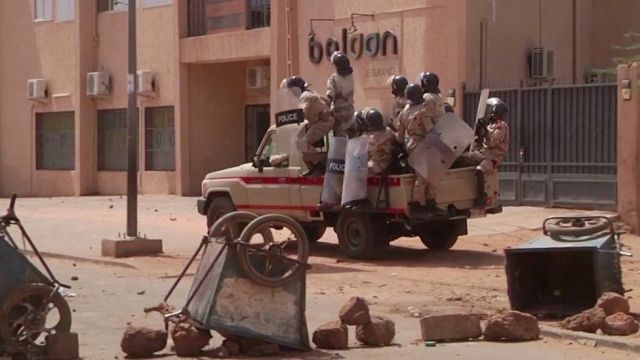 Riot policemen driving towards protesters at a makeshift checkpoint in Niamey, Niger