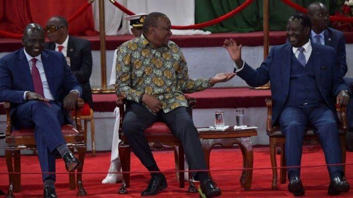 Kenya's President, Uhuru Kenyatta (C) reacts with opposition leader and former Prime Minister, Raila Odinga (R) on November 27, 2019