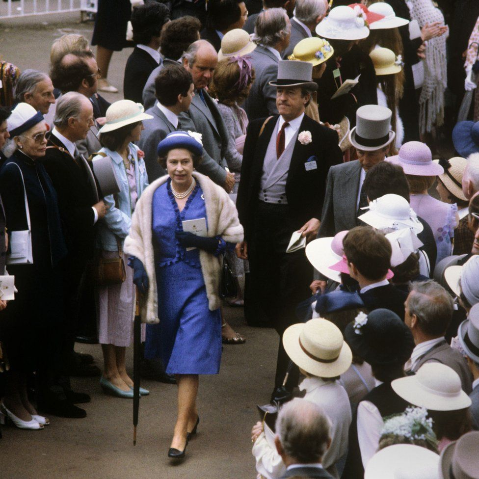 Queen Elizabeth II walking through the crowds at the Royal Ascot race meeting.