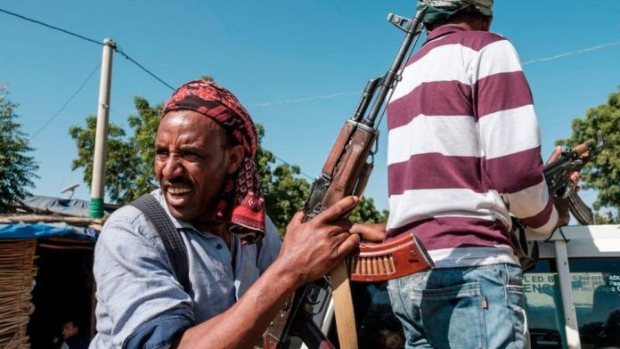 Two members of the Amhara militia ride in the back of a pick up truck, in Mai Kadra, Ethiopia, on November 21, 2020.