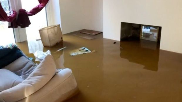 In one home floodwater can be seen filling the living room