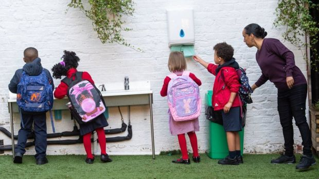 Pupils wash their hands as they arrive on the first day back to school at The Charles Dickens Primary School, last September