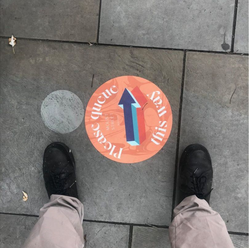 A sign on the ground pointing the way for people to queue