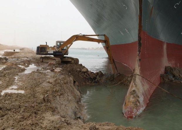 A digger attempts to remove earth around the bow of the Ever Given, which is blocking the Suez Canal, Egypt (25 March 2021)