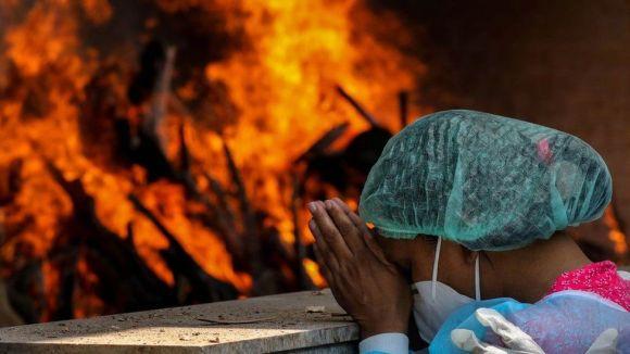 Woman praying near funeral pyre