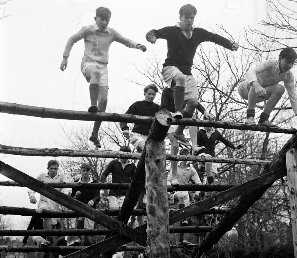 A black and white picture of pupils at Gordonstoun School doing physical training on an obstacle course in 1956
