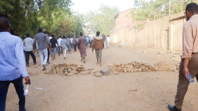 People walking along a road towards a sit-in at the military HQ in Khartoum, Sudan - Monday 8 April 2019
