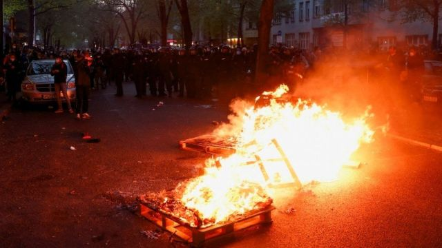 Police officers look on behind burning objects during a left-wing May Day demonstration in Berlin