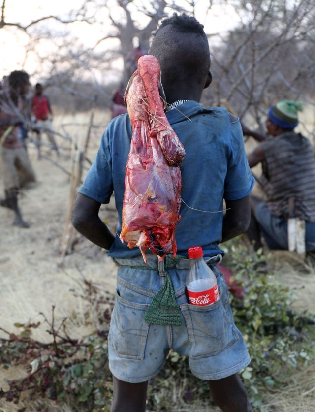 Hadza cargando carne y una botella de Cocacola