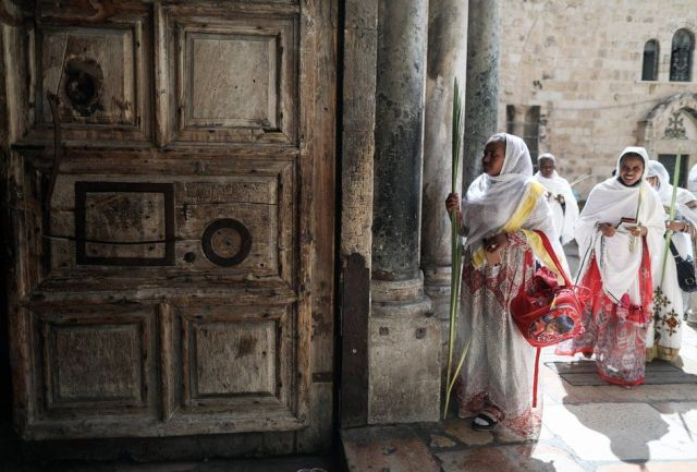 Women dressed in white robes enter the Church.