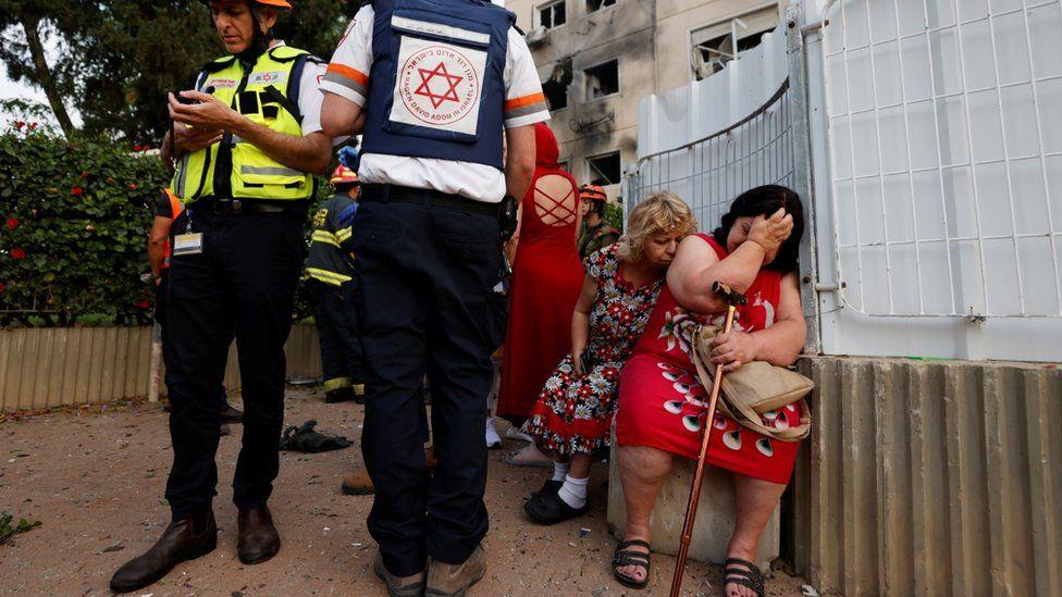 Israeli medics stand near women after a rocket hit a block of flats in Ashkelon, southern Israel (11 May 2021)