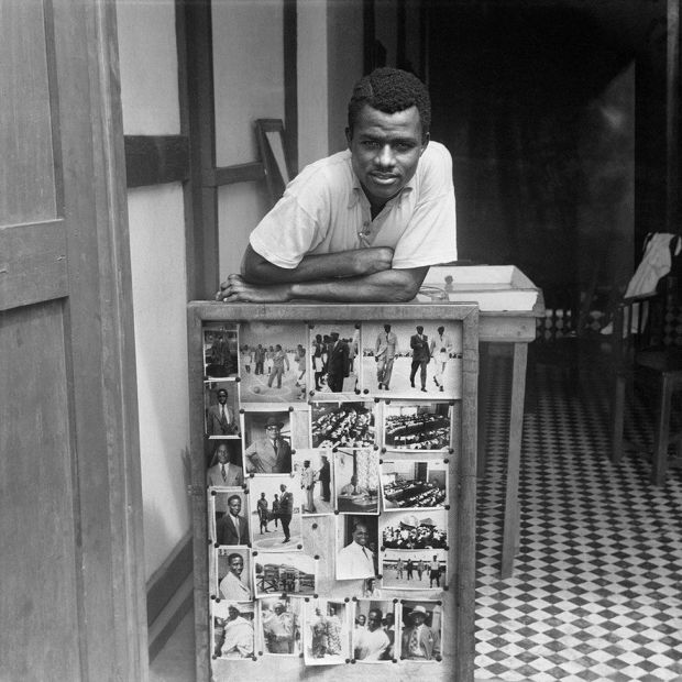 Portrait of James Barnor in front of some of his photographs