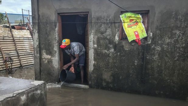 A man using a bucket to clear water from his house