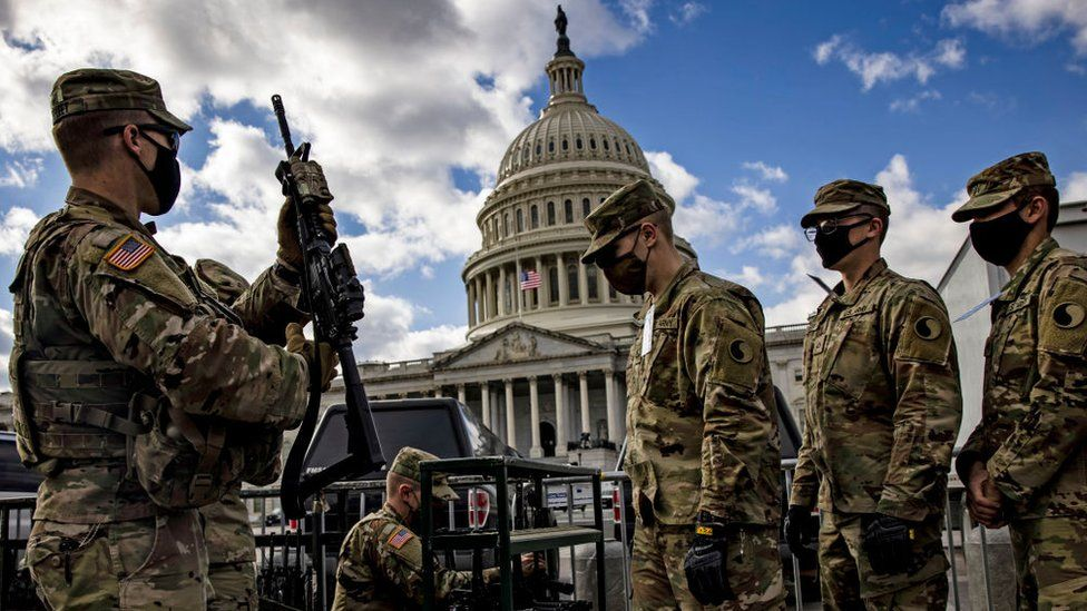 National Guard troops take up weapons as they guard the US Capitol after rioters attacked the building January 2021