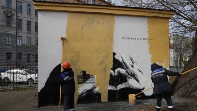 Municipal workers paint over a graffiti image of jailed Russian opposition politician Alexei Navalny