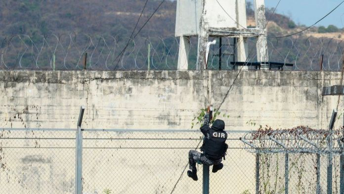 A riot police climb the security fence during a riot at the Guayaquil Regional prison in Guayaquil, Ecuador on September 28, 2021.
