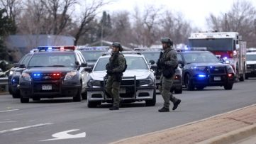 Law enforcement officers stand at the perimeter of a shooting site at King Soopers grocery store in Boulder, Colorado