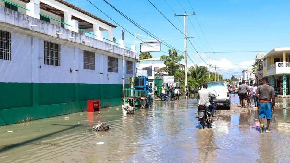Groups of people walk through a flooded street in Les Cayes