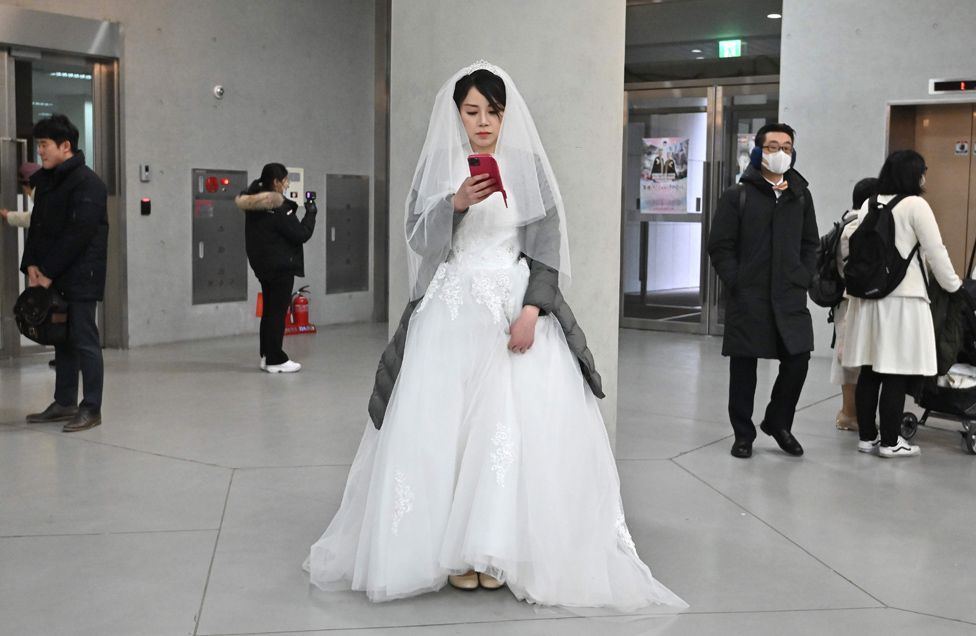Bride takes a selfie at a mass wedding ceremony organised by the Unification Church in South Korea.