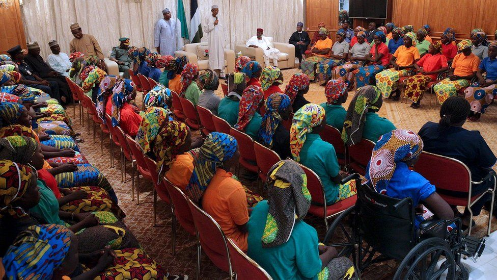 """Nigeria""""s President Muhammadu Buhari (L) addresses the 82 rescued Chibok girls during a reception ceremony at the Presidential Villa in Abuja, on May 7, 2017."""