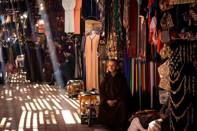 A man sits next to an market stall, with shafts of light piercing through the roof.