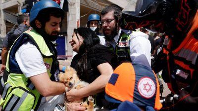 Médicos israelíes ayudan a una mujer después de que un cohete golpeara un centro comercial en Ashkelon, en el sur de Israel (11 de mayo de 2021)