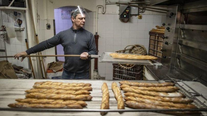 A baker makes baguettes in France