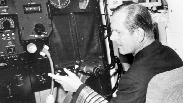 The Duke of Edinburgh, in uniform of the Admiral of the Fleet, sits at the wheel of the nuclear-powered submarine HMS Churchill