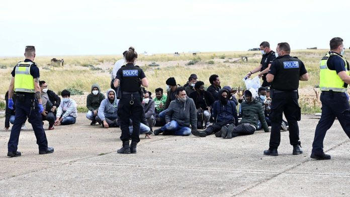 Migrants waiting with police