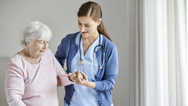 A nurse helping an older woman
