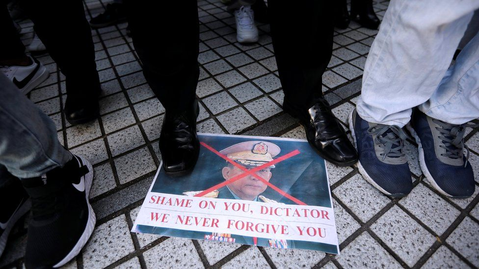 """Myanmar""""s army chief Min Aung Hlaing""""s picture lies on the ground, at a rally by expats living in Japan"""