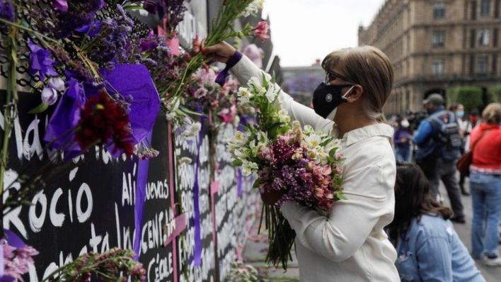 "A woman places flowers beside the names of victims of femicide in Mexico on fences placed outside the National Palace ahead of a Women""s Day protest in Mexico City, Mexico March 7, 2021"