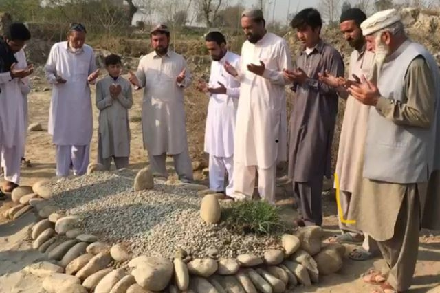 Mourners pay their respects at the graves of Ayesha and Irshad