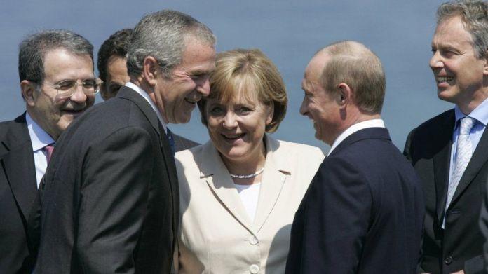 Kryeministri italian Romano Prodi, presidenti francez Nicolas Sarkozy (i fshehur), presidenti amerikan George W. Bush, kancelarja gjermane Angela Merkel, presidenti rus Vladimir Putin dhe kryeministri britanik Tony Blair ndajnë një të qeshur teksa marrin pozicion për një fotografi familjare me G8 të tjerë drejtues,