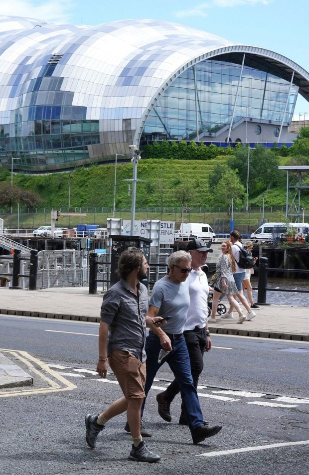 Harrison Ford walking along Newcastle Quayside, with two other men, with the Sage Gateshead in the background