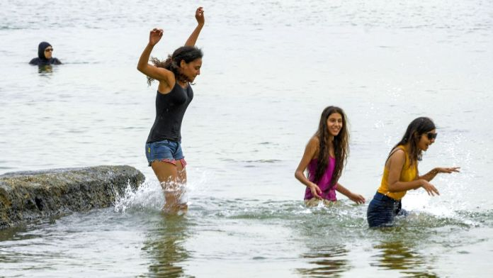Girls cool off in the Mediterranean sea waters at a beach off La Goulette, Tunisia - Tuesday 10 August 2021