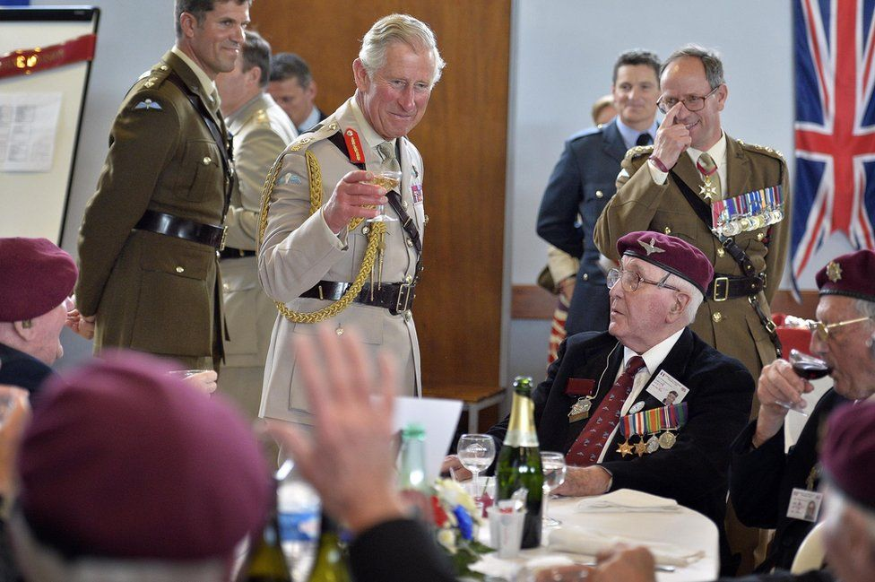 Prince of Wales (centre) raising his glass to D-Day veterans
