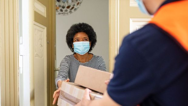 A stock image of a woman being handed a delivery at her front door