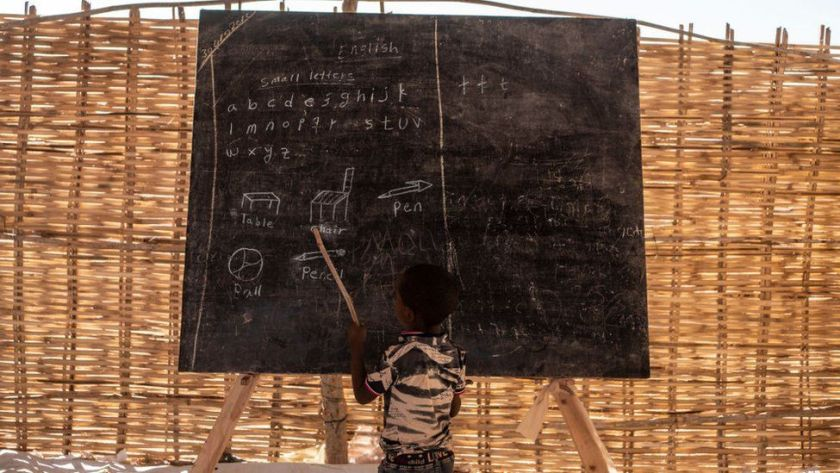 A child reads some English words during his class at the school inside the Um Rakuba camp on January 8, 2021 in Um Rakuba, Sudan